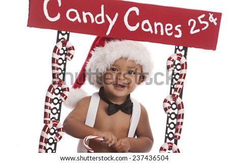 Candy Canes For Sale.  Adorable baby boy selling candy canes.  Isolated on white. - stock photo