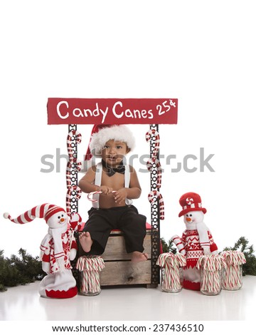 Candy Canes For Sale.  Adorable baby boy selling candy canes.  Isolated on white with room for your text. - stock photo