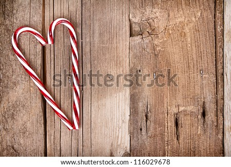 Candy canes in a heart shape on a wooden background - stock photo