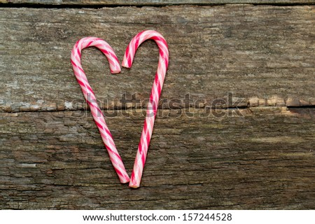 Candy canes in a heart shape on wooden surface - stock photo
