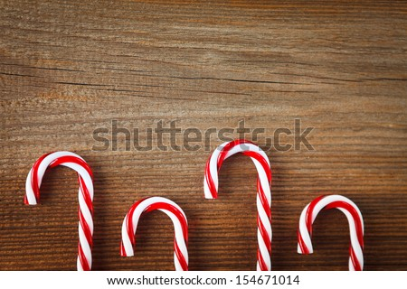 candy canes  on weathered wooden board - stock photo