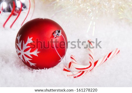 Candy canes with red and silver Christmas ball ornaments on snow background