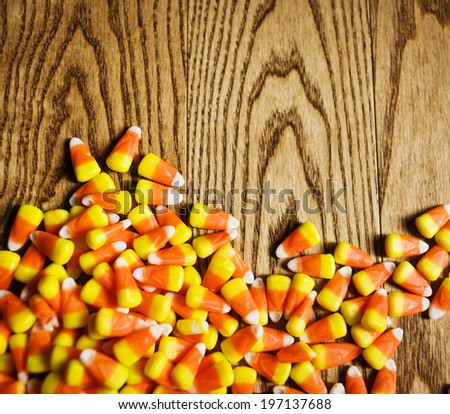 Candy corn that has been spilled on wood. - stock photo