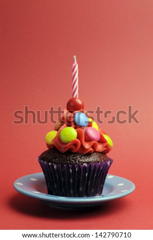 Candy covered chocolate cupcake with red frosting and candy and one birthday candle on red background for Children birthday party - with copy space. - stock photo