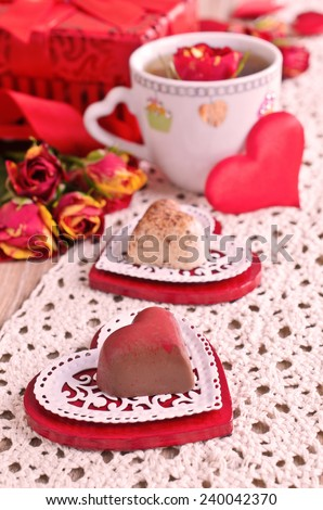 Candy in the shape of a heart on a decorative saucer on the background of the gift boxes, cups of tea and fresh roses