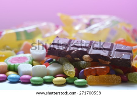 Candy, lollipop, colored smarties, chocolate and gummy bears in foreground and blurred candy packages in pink background