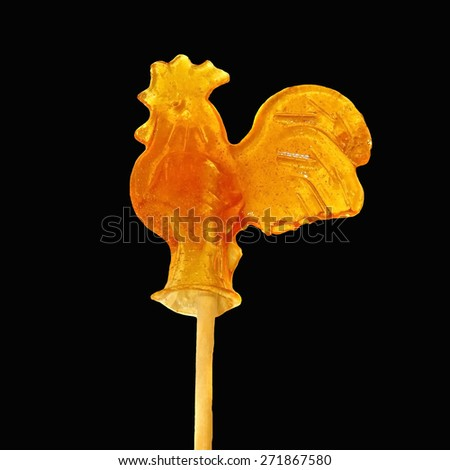 Candy of burnt sugar - cockerel on a stick isolated on black - stock photo