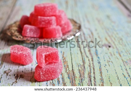 Candy pink jelly sprinkled with sugar lie on beautiful metallic saucer - stock photo