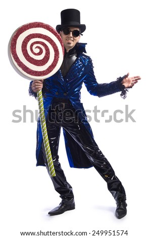 Candyman. Man wearing shiny vinyl pants and morning coat, top hat and goggles, holding giant lollipop. - stock photo