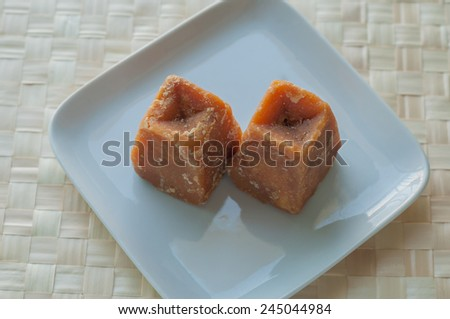 Cane sugar concentrate - an Indian jaggery cakes on white plate - stock photo