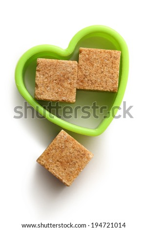Cane sugar cubes in heart form - stock photo