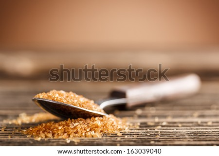 Cane sugar on old wooden spoon  - stock photo