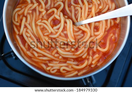 Caned spaghetti cooked on outdoor gas stove. Concept photo of food, preserved,outdoor, camping, survival,surviving,travel, vacation. - stock photo