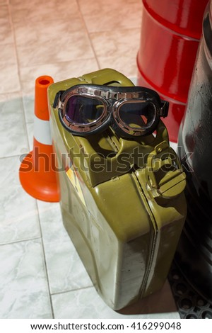 canister of gasoline with sunglasses near the barrels - stock photo