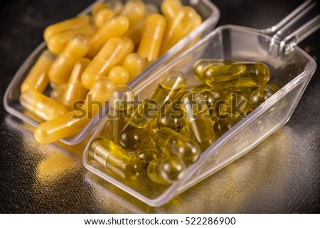 Cannabis extraction capsules infused with shatter and CBD oil isolated over black background