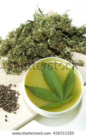 Cannabis healing ointment and marijuana green leaf and seeds - stock photo