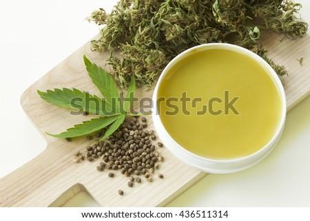 Cannabis healing ointment green marijuana leaf and seeds  - stock photo