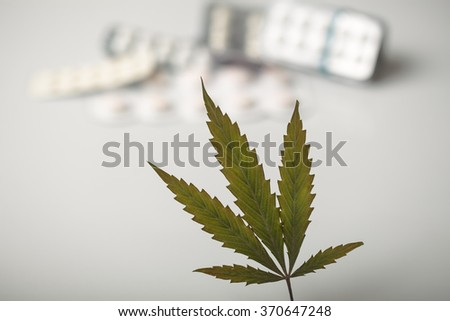 cannabis leaf background tablets - stock photo