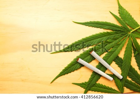 Cannabis leaf, marijuana over wooden texture background with copy space