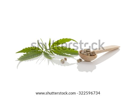 Cannabis seeds on wooden spoon and cannabis leaf isolated on white background. - stock photo