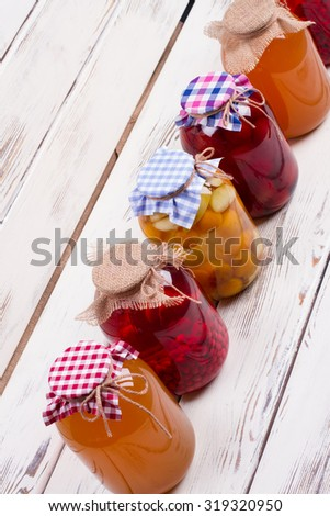 Canned compotes sold in shop. Jars with preservation stand on old boards. - stock photo