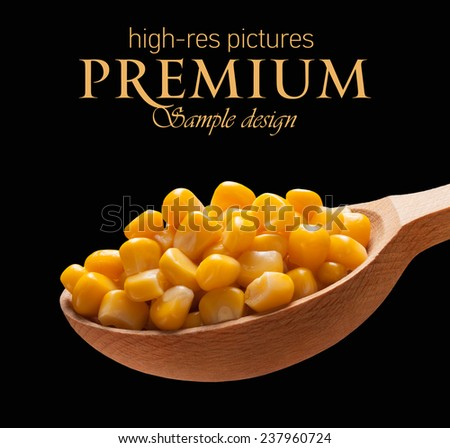 Canned corn in a wooden spoon / kernels on wooden spoon isolated on black background with place for your text  - stock photo