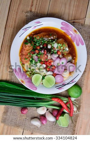 Canned fish salad,Spicy spices of Thailand on wood background.