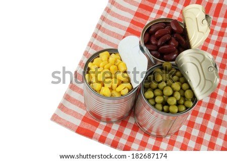 Canned food on tablecloth isolated on white - stock photo