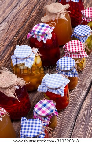 Canned fruits and vegetables homemade. Preservation in glass jars on the old boards. - stock photo