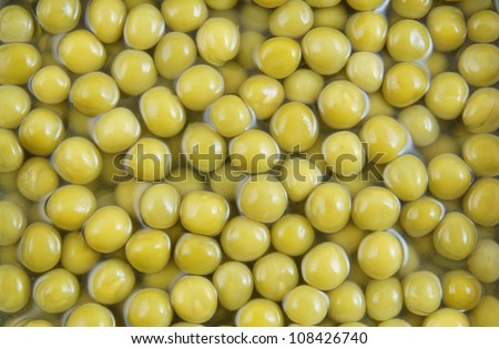 Canned green peas with juice background - stock photo