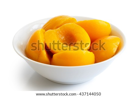 Canned peach halves in bowl isolated on white background. In perspective.