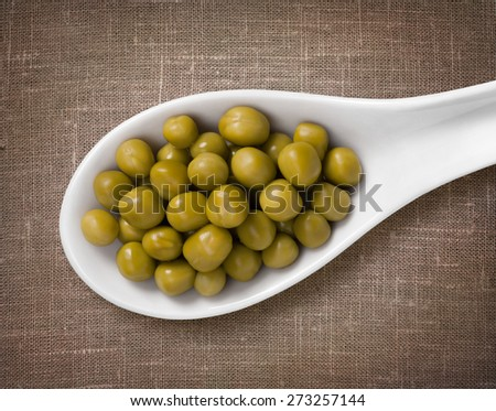 Canned peas in white porcelain spoon / high-res photo of grain in white porcelain spoon on burlap sackcloth background - stock photo