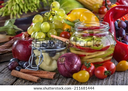 canned pepper and pear with autumn fruits and vegetables around - stock photo