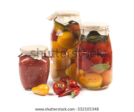 Canned red and yellow salted tomatoes in glass banks with some fresh tomatoes and red peppers isolated on white - stock photo