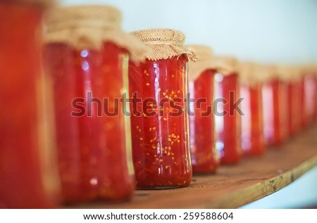 Canned tomatoes in glass jars on wooden shelf. - stock photo