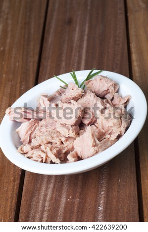 Canned tuna fish in white bowl over wooden background