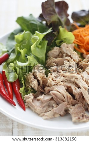 canned tuna fish with fresh vegetable on white dish. tuna. Canned tuna chunks. tuna place on white wooden table. - stock photo