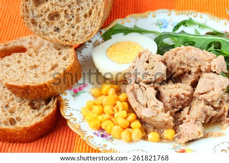 Canned tuna, sweet corn, boiled egg, sliced rye bread with bran and fresh salad leaves (rucola) on a bright color napkin - stock photo
