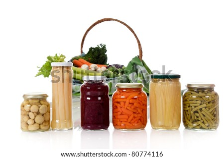 Canned vegetables in jars versus fresh vegetables in basket. Focus on jars. Healthy eating concept. Studio shot. White background. Copy space.