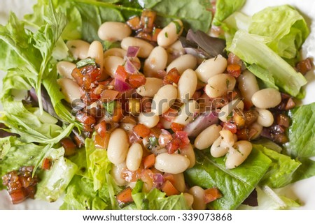 Cannellini bean salad on bed of romaine lettuce with diced sauteed tomato
