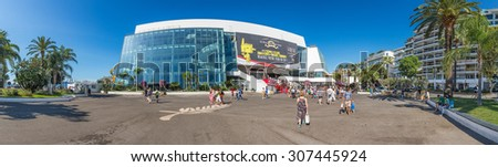 CANNES, FRANCE - AUGUST 17, 2015: People in front of the Cannes Film Festival theatre, a stitched panorama. Cannes is one of the bigest French tourist cities and home to annual film festival.