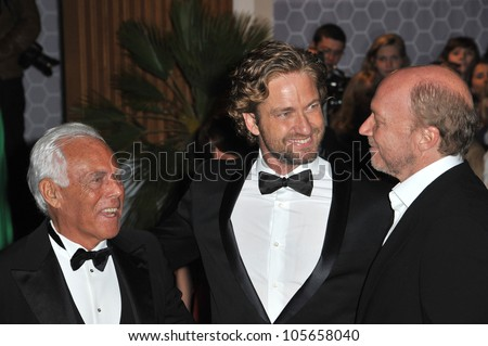 "CANNES, FRANCE - MAY 18, 2012: Giorgio Armani (left), Gerard Butler & Paul Haggis at the ""Haiti Carnaval in Cannes"" party at the 65th Festival de Cannes. May 18, 2012  Cannes, France"