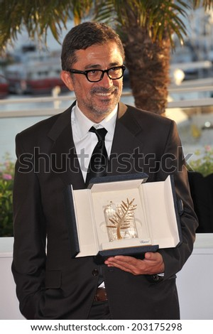 """CANNES, FRANCE - MAY 24, 2014: Nuri Bilge Ceylan, winner of Palme d'Or for """"Winter Sleep"""", at the awards photocall at the 67th Festival de Cannes.  - stock photo"""