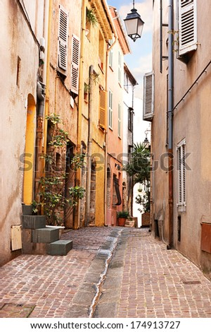 CANNES, FRANCE - MAY 7, 2013: The cozy old street with green plants in the pots  and drain in the middle of the road, on May 7 in Cannes.