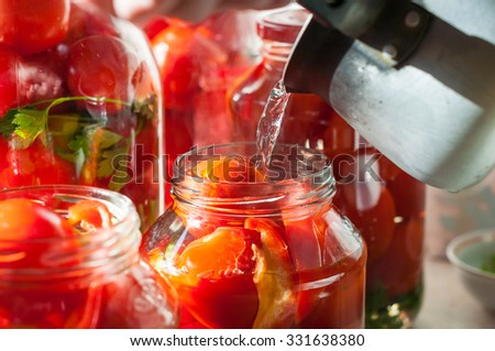 Canning process of tomato in mason jar. On background is few jars with tomatoes. Conservation and cooking - stock photo