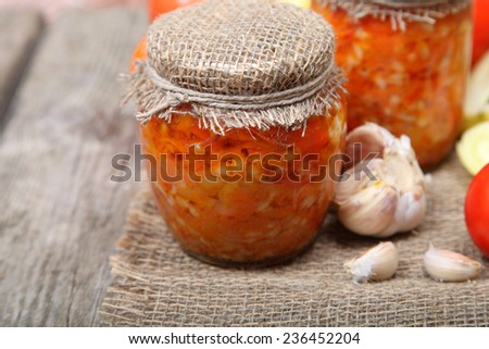 Canning vegetables in the banks on wooden background - stock photo