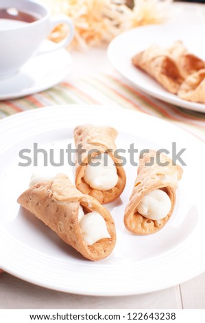 Cannoli tubes pastry on the plate and tea - stock photo