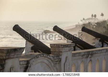 Cannon of Cape Coast Castle and Beautiful Beach with Palms - stock photo