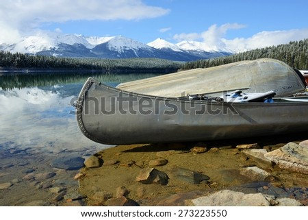 Canoe and boat on the lake shore with beautiful mountains in Jasper National Park, Canada, Unesco World Heritage - stock photo