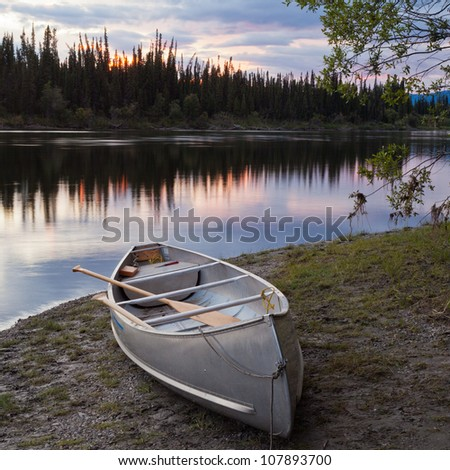 Canoe and paddles beached on shore of beautiful Teslin River in the remote wilderness of Yukon Territory, Canada, the river surface reflecting delicate sunset colors - stock photo
